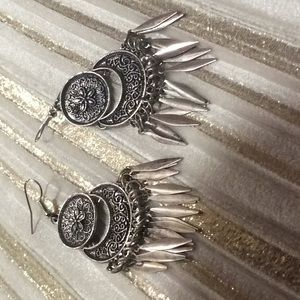 Silver color dangling earrings.